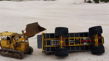 The crashed four-wheel-drive lies on its side in the Lancelin dunes.