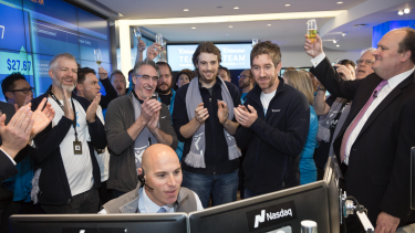 Atlassian founders Scott Farquhar and Mike Cannon-Brookes watch as shares in their company begin trading in New York.