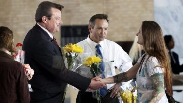 Larissa Boose Williams, right, and her daughter Sedona, 10, hand out flowers to Tony London, left, and Tim Bostic after they become the first couple to obtain a gay marriage in the state of Virginia.