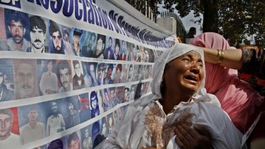Looking for answers ... a grieving mother weeps during a rally in Srinagar as she looks at a wall of photographs of missing men and boys about 8000 of whom have disappeared in the last 20 years.