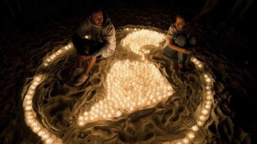 Members of the World Wildlife Fund sit among lit candles forming a representation of the Earth during a demonstration in a beach of Cancun.