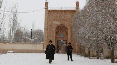 Tense region: Uighur men walk out of a mosque in Ujme township, Xinjiang.