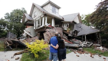 In this February 23, 2011 photo Murray and Kelly James look at their destroyed house in central Christchurch, a day after the deadly earthquake.