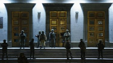 Armed men stand guard at the local government headquarters in Simferopol, Crimea.