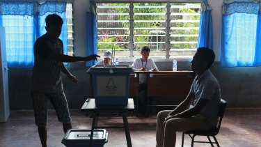 A man casts his ballot as an electoral worker, left, looks on during the presidential election at a polling station in Dili, East Timor.