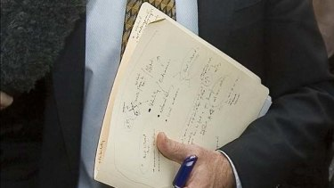 Telltale folder ... Independent MP Rob Oakeshott returns to his office after meeting with his fellow independents Tony Windsor and Bob Katter at Parliament House.