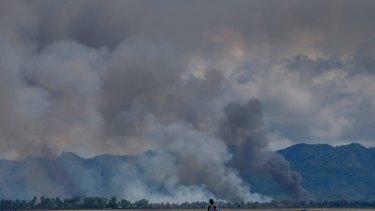 A Bangladeshi boy walks towards a parked boat as smoke rises from across the border in Myanmar, at Shah Porir Dwip, Bangladesh.