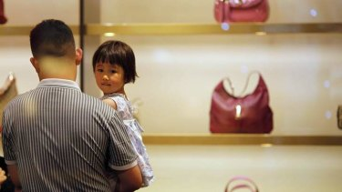 Growing market: A man and his daughter in a Gucci shop in Shanghai.