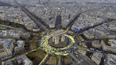 The Arc de Triomphe roundabout painted yellow by climate change activists during the Paris conference.