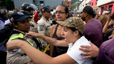 A woman argues with the police during a protest for food in Caracas, Venezuela.