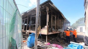 Widespread damage ... Workers extinguish flames after rioters caused $60m damage  on July 20, 2013 on Nauru Island.