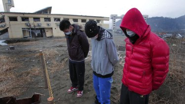 High-school students mourn the victims of the March 11, 2011 earthquake and tsunami, in Rikuzentakata, northeastern Japan, Sunday