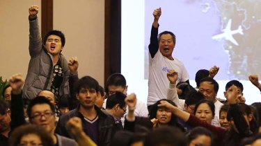 """""""Return our families"""": Family members of passengers onboard MH370 raise their fists in protest at a government briefing over the missing plane."""