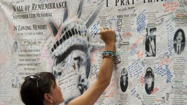 A woman writes on a wall near the remembrance memorial.