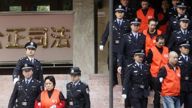 Xie Caiping, left, is taken from court after her sentencing.