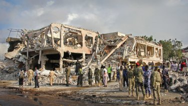 Somali security forces and others search for bodies near destroyed buildings in Mogadishu on Sunday.