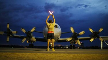 A ground controller guides a Royal Australian Air Force P-3 Orion to rest in Perth after another day of scouring the Indian Ocean.