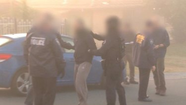 Australian Federal Police arrest a man during a raid on an Islamic store in Logan, south of Brisbane.