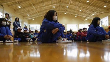 With their faces covered by masks, these children are restricted to indoor activities at Fukushima city's youth centre gymnasium.