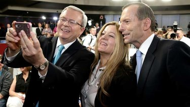 A woman requests a photo with Prime Minister Kevin Rudd and Opposition Leader Tony Abbott at Rooty Hill RSL in Western Sydney.