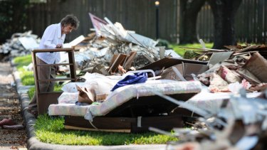 Antoinette Porcarello views her flood-damaged possessions piled in the front yard in the aftermath of Hurricane Harvey in Houston.