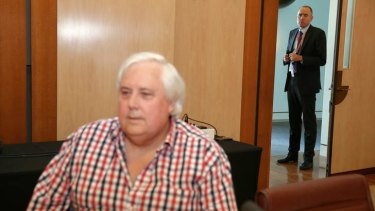 Clive Palmer adviser Ben Oquist stands behind the PUP leader before a press conference.