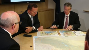 Prime Minister Tony Abbott and ASIO director-general Duncan Lewis look at the secret-but-not secret maps at ASIO Headquarters on Wednesday.