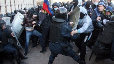 Pro-Russian supporters clash with members of the riot police as they storm the regional administration building in the eastern Ukrainian city of Donetsk.