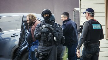 A man is led from a house by police during a terror raid in Ballarat Road, Braybrook, on Saturday, August 6.