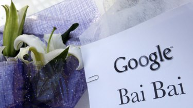 """A sign, which reads """"Google Bai Bai (bye bye)"""" is seen near flowers, left by visitors outside the Google China headquarters in Beijing."""