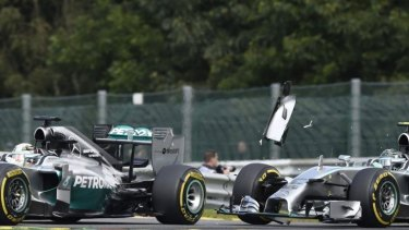 Debris flies off Rosberg's car after it collides with Lewis Hamilton's Mercedes. The collision punctured a wheel on Hamilton's car.