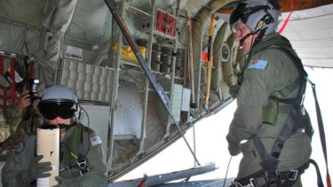 Narrowing the search area ... Loadmasters Sergeant Adam Roberts (left) and Flight Sergeant John Mancey prepare to launch a water-activated buoy from the Hercules C-130J.
