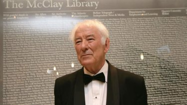 Nobel prize-winning poet Seamus Heaney stands before a large glass panel listing all the benfactors before the offical opening of Queens Unversity's new McClay Library, Belfast. Nobel Laureate Heaney has died at the age of 74, sources said on August 30, 2013. AFP PHOTO / PAUL MCERLANE
