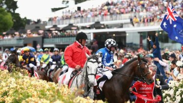 Dwayne Dunn riding Araldo (in background) is frightened by a racegoer holding an Australian flag as he returns to the mounting yard on Melbourne Cup Day.