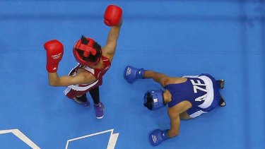 Japan's Satoshi Shimizu stands over Azerbaijan's Magomed Abdulhamidov after knocking him down.