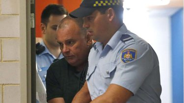 Glen McNamara is escorted from Kogarah local court after his arrest.