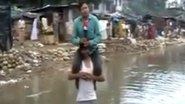 Reporter Narayan Pargaien, of  the News Express channel, sits on the shoulders of a flood victim.