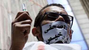 """Dissent stifled: An Egyptian journalist protests against the country's Interior Ministry, which is accused of targeting journalists. The tape across his mouth reads """"the blood of a journalist is not cheap""""."""