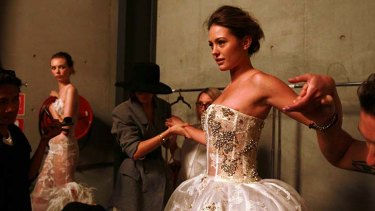 Model Jesinta Campbell backstage in one of Lam Yu's white gowns.