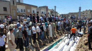 Mourners gather at a mass burial for victims of the artillery barrage in Houla.