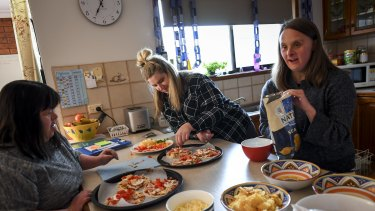 Melanie, Belinda and Jess prepare food for their party to celebrate one year of living together.