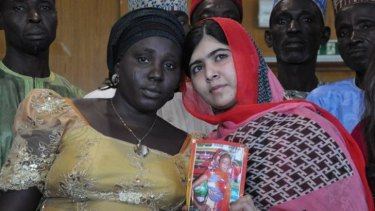 Pakistani activist Malala Yousafzai holds a picture of kidnapped schoolgirl Sarah Samuel with her mother Rebecca Samuel, during a visit to Abuja, Nigeria.