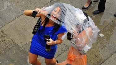 Race fans take shelter from the rain at Flemington.