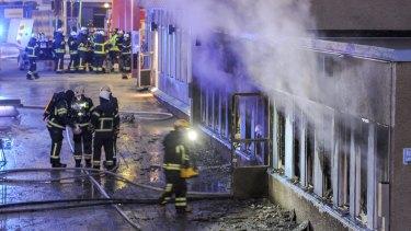 Firemen at work outside the mosque in Eskilstuna, Sweden,