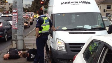 A witness said the removalists were handcuffed by police and thrown to the ground.