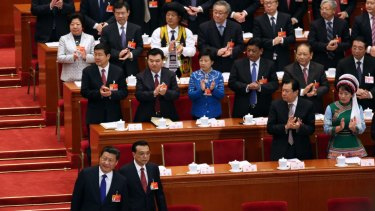 Members of the National People's Congress applaud as President Xi Jinping, front left, and Premier Li Keqiang, right, take their seats.