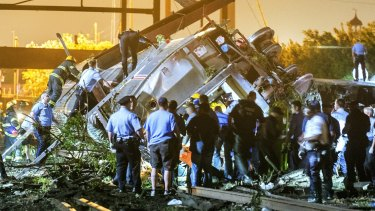 Rescue workers climb into the wreckage of the derailed Amtrak train in Philadelphia.
