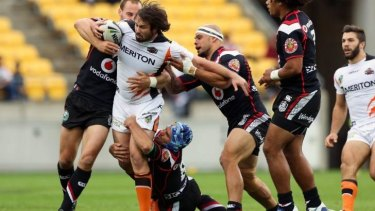 The Tigers' Aaron Woods is wrapped up by the Warriors' defence.