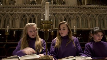 History girls: (From left) Choristers Abby Cox, Poppy Braddy and Chloe Chawner with their hymn books at  Canterbury Cathedral.