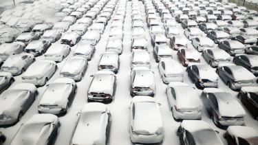 Cars are covered by snow in parking lot at O'Hare International Airport in Chicago.